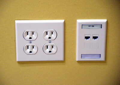The new network cabling outlet, right, is aligned with and the same color as the existing outlet, with each jack labeled.
