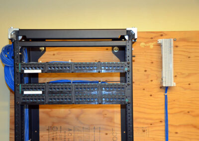 Front view of a wall-mounted cabling rack with a 24-port and a 48-port patch panel installed.