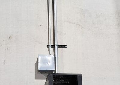 Wall mounted network cabinet in a warehouse with cabling securely protected in a metal sleeve.